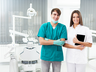 Dental office staff members smiling and standing next to each other