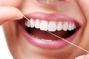 A beautiful, healthy smile being maintained with dental floss